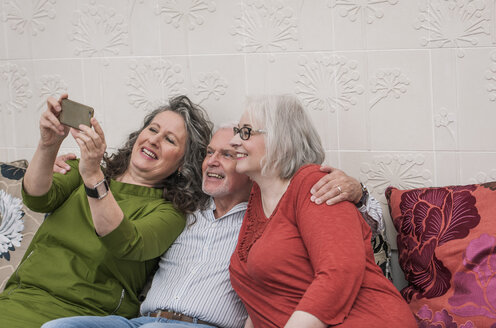 Happy seniors taking selfie on couch - CUF22764