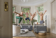 Boys in living room jumping in mid air - CUF22797