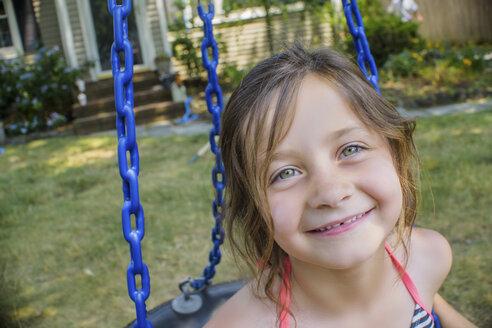 Portrait of cute girl playing on swing in garden - ISF08793