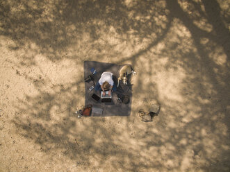 Bird's eye view of woman sitting on blanket with dog using laptop - ONF01115