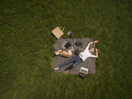 Bird's eye view of woman lying on blanket on meadow with dog and utensils - ONF01124