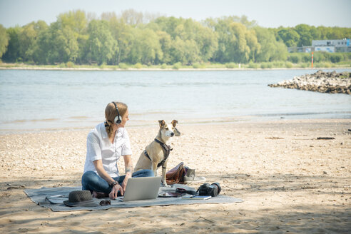 Woman sitting on blanket at a river with dog wearing headphones and using laptop - ONF01127