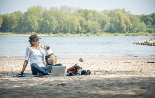 Woman sitting on blanket at a river with dog and laptop - ONF01130