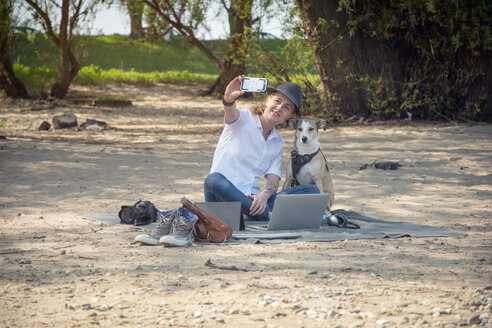 Smiling woman sitting on blanket on beach with dog taking a selfie - ONF01133