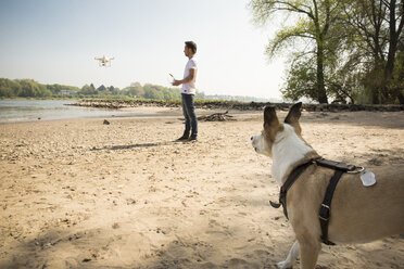 Man with a dog flying drone at a river - ONF01136
