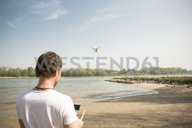 Man flying drone at a river - ONF01145 - noonland/Westend61