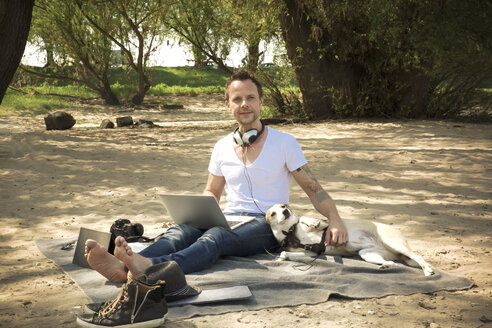 Portrait of man with dog sitting on blanket at a beach using laptop - ONF01151