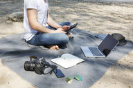 Man sitting on blanket at a beach using tablet - ONF01154