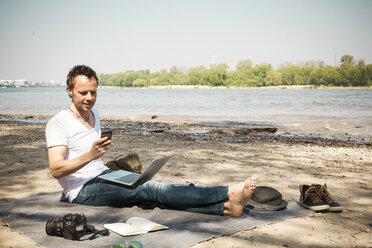 Man sitting on blanket at a river using laptop and cell phone - ONF01157