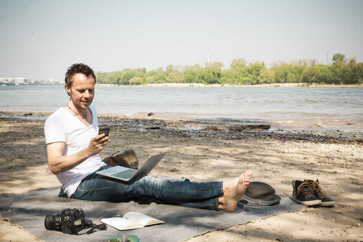 Man sitting on blanket at a river using laptop and cell phone - ONF01157 - noonland/Westend61