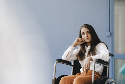 Young handicapped woman sitting in wheelchair, looking worried - KNSF03909