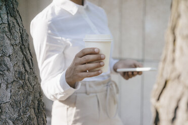 Young businesswoman carrying cup of coffee and a smartphone - KNSF03924