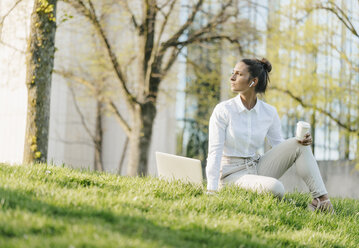 Young businesswoman taking break, using laptop, sitting in grass and drinking coffee - KNSF03927