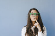 Young woman wearing pixel glasses, putting finger on mouth - KNSF03936