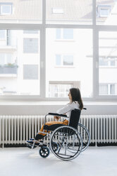 Young handicapped woman sitting in wheelchair - KNSF03945