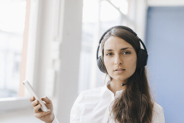 Young woman using smartphone, wearing headset - KNSF03948