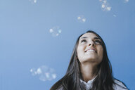 Pretty young woman playing with soap bubbles - KNSF03954