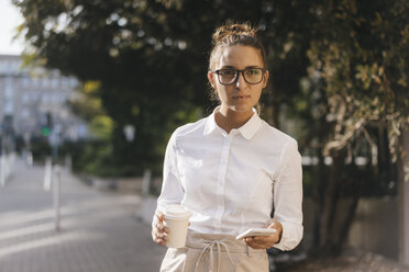 Young businesswoman carrying cup of coffee and a smartphone - KNSF03966