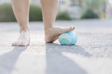 Foot of young woman stepping on globe - KNSF03972