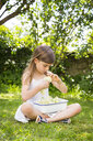 Little girl sitting on meadow in the garden with bowl of picked elderflowers - LVF07022