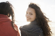 Young women wrapped in knitted shawl on cold windy day - CUF22840