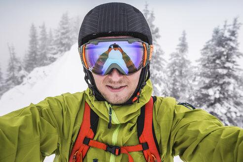 Close up of male skier wearing ski goggles taking selfie on mountain at Kranzegg, Bavaria, Germany - CUF22846