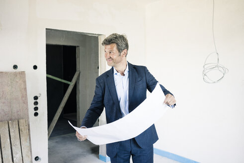 Smiling architect with blueprint in building under construction - MOEF01233