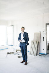 Portrait of smiling architect in building under construction - MOEF01239
