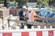 Man in suit with tablet talking to construction worker on construction site - MOEF01254