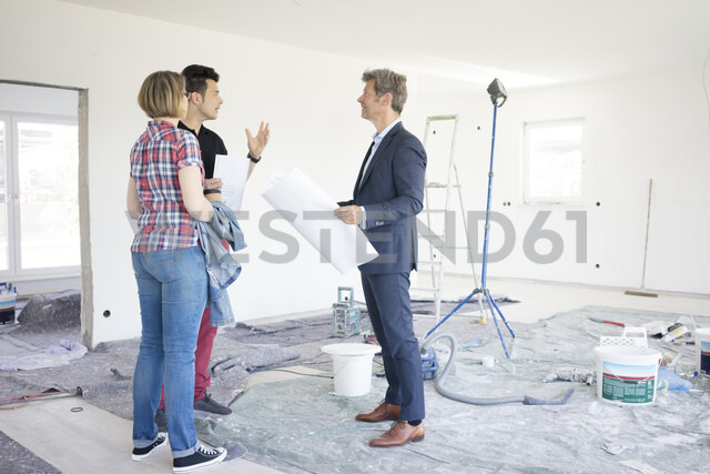 Man in suit talking to couple in unfinished  building - MOEF01266