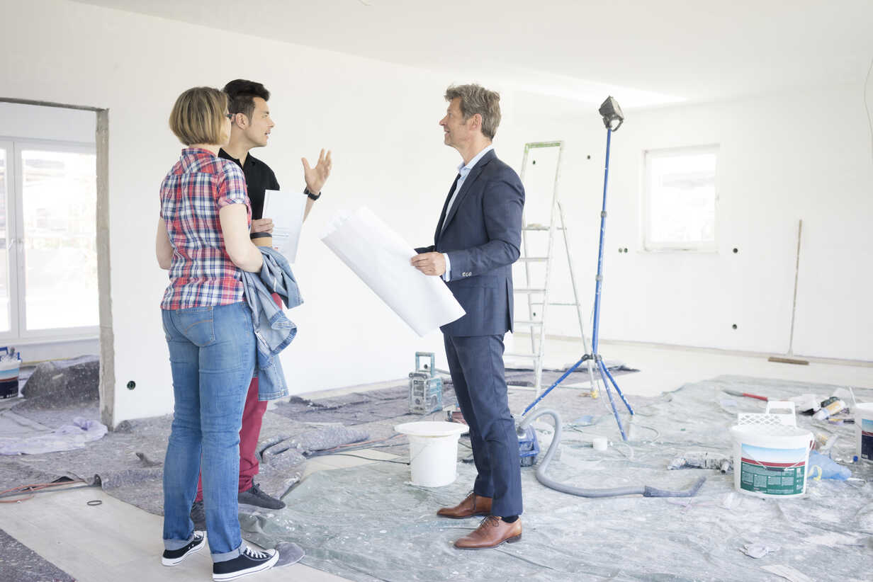 Man in suit talking to couple in unfinished  building - MOEF01266 - Robijn Page/Westend61