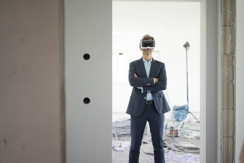 Man in suit wearing VR glasses in building under construction - MOEF01278