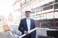 Portrait of confident architect wearing hard hat on construction site - MOEF01293