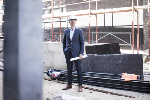 Confident architect wearing hard hat standing on construction site - MOEF01296