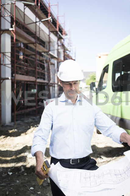 Architect with blueprint wearing hard hat on construction site - MOEF01299 - Robijn Page/Westend61