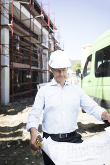 Architect with blueprint wearing hard hat on construction site - MOEF01299