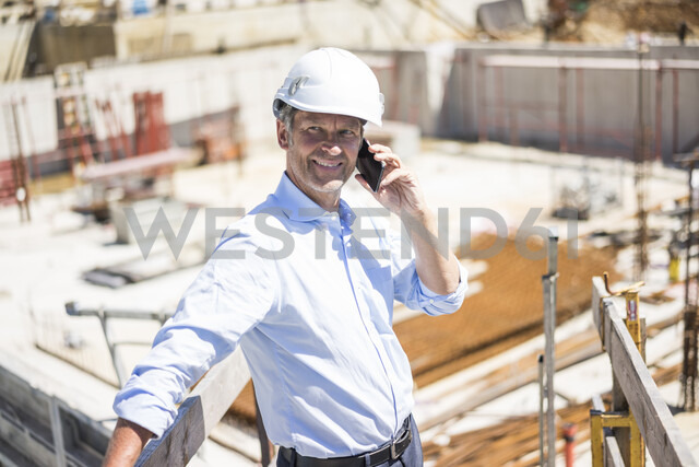Smiling man wearing hard hat on cell phone on construction site - MOEF01305 - Robijn Page/Westend61