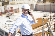 Smiling man wearing hard hat on cell phone on construction site - MOEF01305