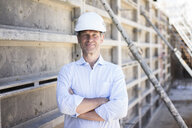 Portrait of confident man wearing hard hat on construction site - MOEF01311
