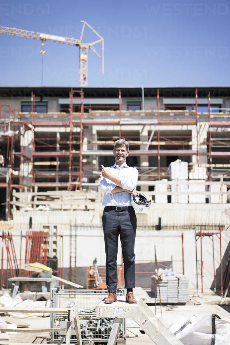 Portrait of happy man standing on construction site - MOEF01314 - Robijn Page/Westend61