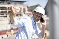 Smiling man wearing hard hat on cell phone on construction site - MOEF01317