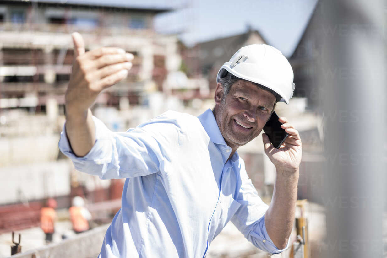 Smiling man wearing hard hat on cell phone on construction site - MOEF01317 - Robijn Page/Westend61