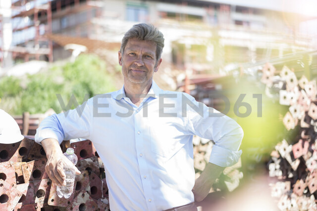 Portrait of confident man holding bottle of water on construction site - MOEF01320 - Robijn Page/Westend61