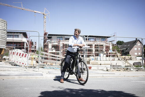 Man with e-bike on construction site looking around - MOEF01323