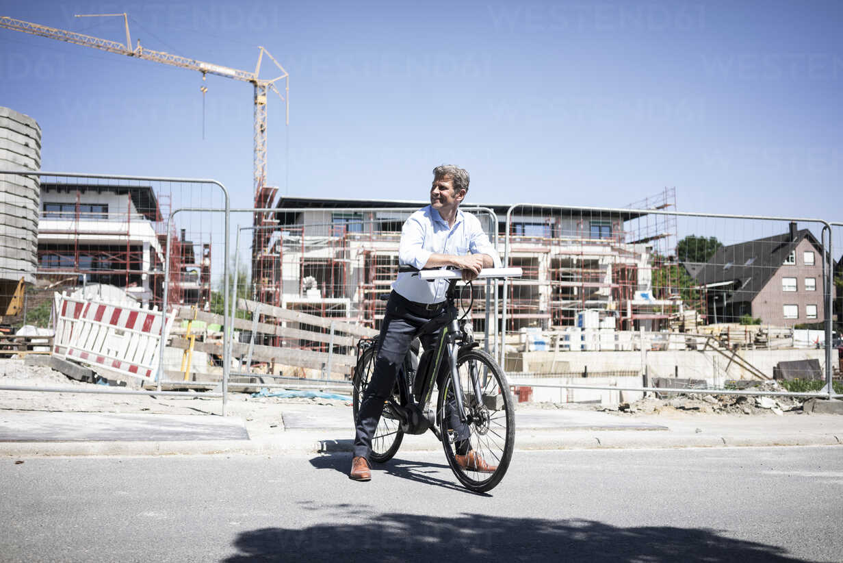 Man with e-bike on construction site looking around - MOEF01323 - Robijn Page/Westend61