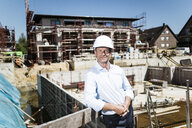 Portrait of confident man wearing hard hat on construction site - MOEF01326