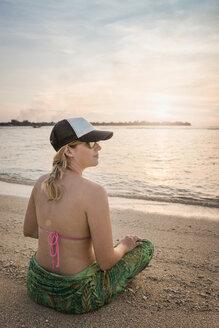 Young woman sitting cross legged on beach, Gili Meno, Lombok, Indonesia - CUF23004