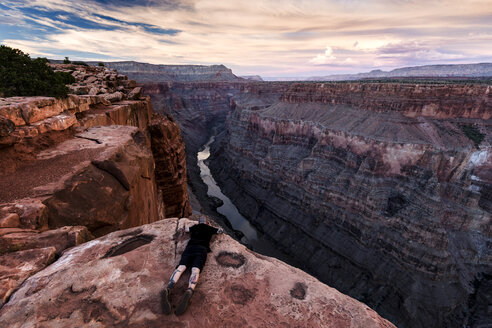 Man lying on rock, looking at view, Torroweap Overlook, Grand Canyon, Torroweap, Arizona, USA - CUF23067