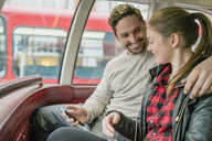 Young couple on front seat of double-decker, Kings Road, London, UK - CUF23079
