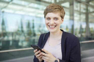 Portrait of blond businesswoman using smartphone - PNEF00683